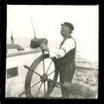 Photo: Collection Claude May Belley- Photographie de Elzéar Lefebvre-Boulanger, prise le 14 juillet 1906, à la barre d'un des nombreux navires qu'il a piloté.